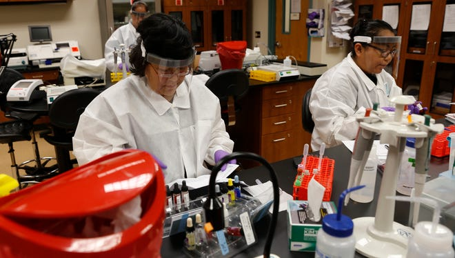 Lucinda Begay, left, and Neldra Castillo participate in a lab Friday during class at San Juan College in Farmington.