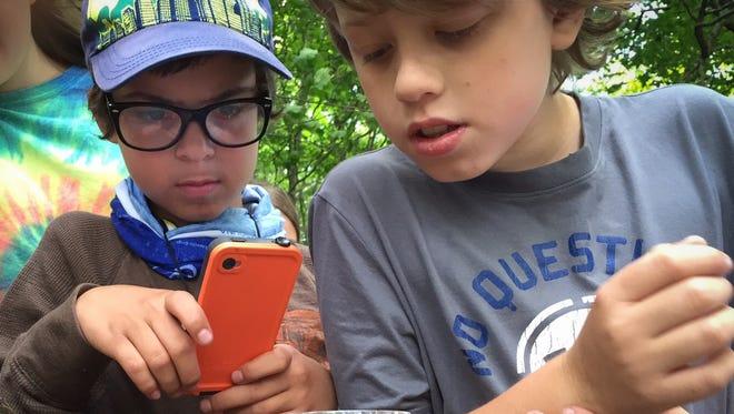 Adam Edge, right, watches as a fellow ecoEXPLOREr photographs a salamander during a program event near the Blue Ridge Parkway last year.