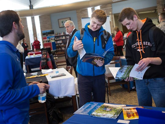 Senior Colton Fockler, 17, and junior Alex Mayer, 16, look over information and talk with Lake Superior State University representative Phil Lepper during a college fair Thursday, Feb. 11, 2016 at Port Huron Northern High School.