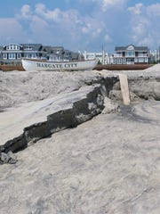 Sand is eroded away on the beach in Margate on Wednesday, Aug. 2, 2017, after water from one of three large ponds on the beach was pumped out to sea. On Tuesday, Aug. 22, 2017 a federal appeals court refused to halt the project in Margate. Residents named the bacteria-laden water that pooled after a storm 'Lake Christie.'The dune project resumed in Margate last weekend after a federal judge overruled a state judge's decision to stop it.Margate homeowner Anne Rubin says that the project has made going to the beach like going to a construction site.