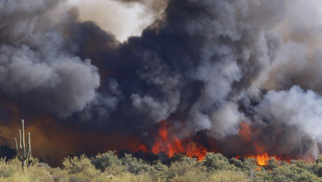 A Wildfire consumes brush Wednesday, June 17, 2015 in Kearny, Ariz.