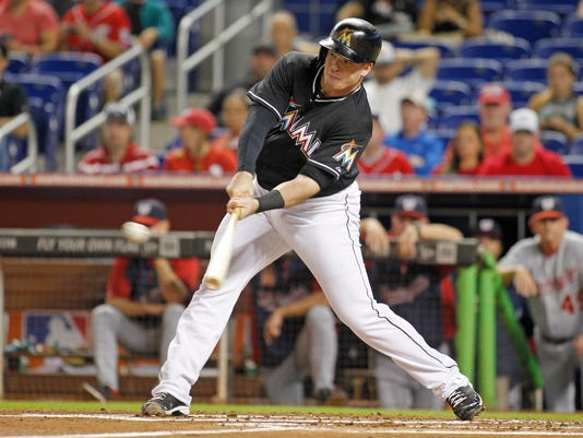 Miami Marlins first baseman Justin Bour hits an RBI single in the first inning against the Washington Nationals during a baseball game in Miami, Saturday, Sept. 20, 2014. (AP Photo/Joe Skipper)