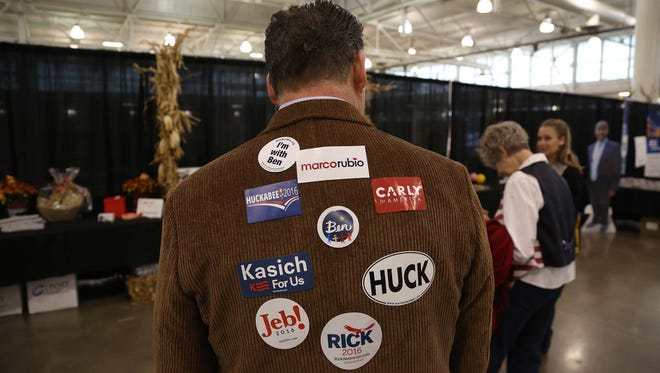 An attendee of the Growth and Opportunity Party collects candidate stickers on his back on Saturday, Oct. 31, 2015 at the Varied Industries Building in Des Moines.