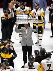 Pittsburgh Penguins owner Mario Lemieux hoists the