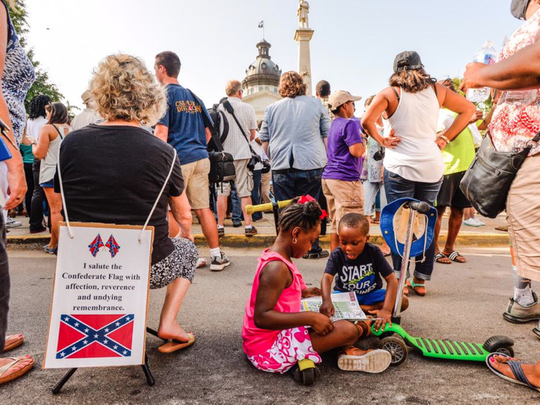 Charlene Stoll Hale honors hers Confederate ancestors. Alana and Gracen Wilson wait for flag removal.