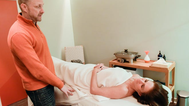 Kur Wellness Studios owner Troy Teeboom talks with Marina Nonnenmacher, Middletown, who is on a massage table.