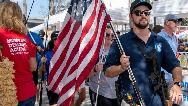 Gun-rights activists march their way through shoppers at the green market Saturday, Jan. 4, 2020, in West Palm Beach. State law allows people to carry weapons to go fishing. {STEVE MITCHELL/for palmbeachpost.com]