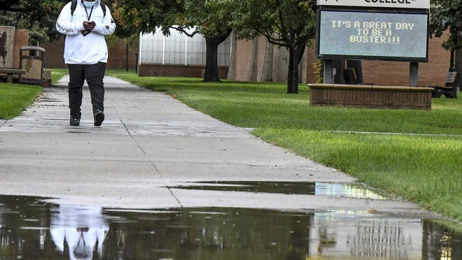 Dave Desansapa is reflected in a water puddle from overnight rain showers on the Garden City Community College campus Wednesday as he walks between classes in a light drizzle and temperatures in the upper 30s. Desansapa is a GCCC freshman from Washington, D.C.