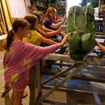 """Prop Master Emily Gardner shows kids the """"Crock"""" used in the Peter Pan Production in the prop shed at the Barn Theatre during Backstage Xperience."""