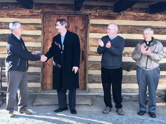 The Corning Rotary Club recently awarded a grant to the Corning-Painted Post Historical Society to help restore its Wixon Road Log Cabin. From left are Leon Golder, historical society board president, Corning Rotary President Ted Goldwin, Corning Mayor-elect William Boland, and former historical society Vice President David Anderson.