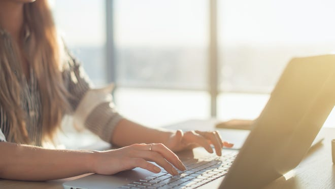 Female writer typing using laptop keyboard at her workplace in the morning. Woman writing blogs online, side view close-up picture