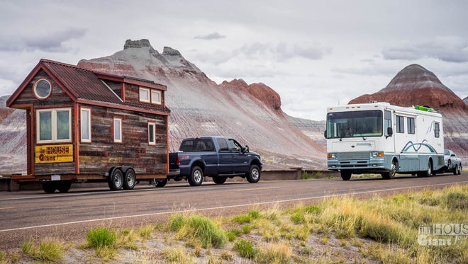 A tiny house is pulled by a truck in the Petrified Forest and moves close to a recreational vehicle.