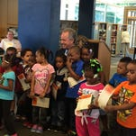 Children post for a photo with Mayor Greg Fischer after receiving their 2015 Cultural Passes at the Shawnee Public Library.