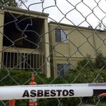 Days after an apartment fire charred six units, fencing blocks the public from accessing the structure and caution tape warns of asbestos contamination.
