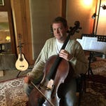Jeff McAuley sits in the recording studio he built on the West Side of Binghamton. McAuley is a lifelong cello player and produces and composes music.