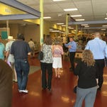 Robert Scarpa gestures to a tour group of real estate agents and brokers on June 23 at Landis MarketPlace. Scarpa is its manager.