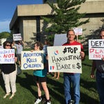 Anti-abortiion activists demonstrate Saturday outisde The Family Leader Summit in Ames, Iowa. Other groups demonstrating included atheists and people opposed to corporate influence in campaigns.