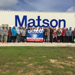 Government of Guam representatives and local military members pose for a photo in front a 40-foot container at the Guam National Guard facility in Barrigada on Aug. 31 which had more than $35,0000 worth of supplies purchased with money donated in two boot drives held in August.  The supplies are being shipped to Saipan for those affected by Typhoon Soudelor.