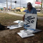 Homeless artist Jon Masters shows off his art work, while his service dog Sheba catches some sleep.