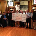 Joe Nuxhall Miracle League Fields representatives accept a $15,000 grant from Character and Courage team members at Green Diamond Gallery.