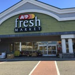 Workers replace an A&P sign with an Acme sign in October. Acme held an official grand opening there on Oct. 25.