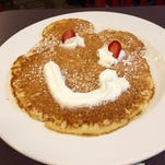 The Kids Sweet Cream Pancakes at Hicks and McCarthy in Pittsford resemble an animal character with ears, eyes outlined in whipped cream and two strawberries, and a stream of whipped cream for the grin.
