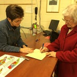 Jewel Hall, right, who recently moved to Dover from Louisville, Ky., is assisted with voter registration paperwork by Stewart County Administrator of Elections Nellie Anderson, left.