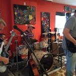 Chris Hart, brew master and co-owner of Cape Coral Brewing Company, plays the drums during a Sunday open music jam at the brewery. Shawn Russell, left, and Scott Quittem, right, play guitars.