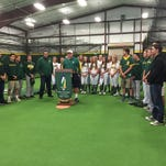 Bishop Manogue softball and baseball players help celebrate at the ribbon-cutting ceremony for the school's indoor practice facility.