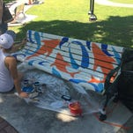 "Merritt Island artists, Solstice Backus-Little, paints a bench in Cocoa Village. Her work is named ""Sharks."""