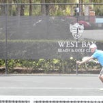 Jared Kalpin, West Bay Beach & Golf Club's director of tennis, shows how keeping the head down and trying to see the ball hit the racket is akin to a baseball batter's skills.