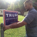 Billy Prater adjusts a Donald Trump sign on his fence in Beech Creek, W.Va., in Mingo County. Laid off from the coal mines, he had been out of work for more than a year. Now he works for the railroad, but the major customer is the collapsing coal industry, so his work is unsteady.