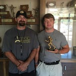 Oak Grove senior Sam Philley (right) and defensive coordinator Lawson green - defensive coordinator accept the Cooper Buick GMC High School Hero Award.