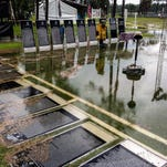 Walls of the traveling Vietnam Memorial Wall lie in puddles.