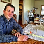 Great Falls businessman John Paul does paperwork for his Pre-Engineered Fire Systems business on a long table in his house. He plans to construct a large building northeast of town for his crew to assemble large packaged fire suppression pump houses.