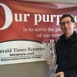 Manitowoc HTR Media General Manager Lowell Johnson holds the crystal trophy presented to the Herald Times Reporter for winning top honors in its division in the 2014 Better Newspaper Contest sponsored by the Wisconsin Newspaper Association.