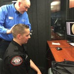 Justin Jenkins with the OTC Hearing Instrument Science program examines Greene County deputy Ryan McKinley.