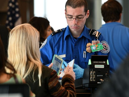 A TSA officer checks in a passenger at the security checkpoint at McGhee Tyson Airport in 2017. Passengers on commercial flights will need identification that meets Real ID Act standards beginning Oct. 1, 2020. Tennessee will start issuing Real ID-compliant driver's licenses on July 1.