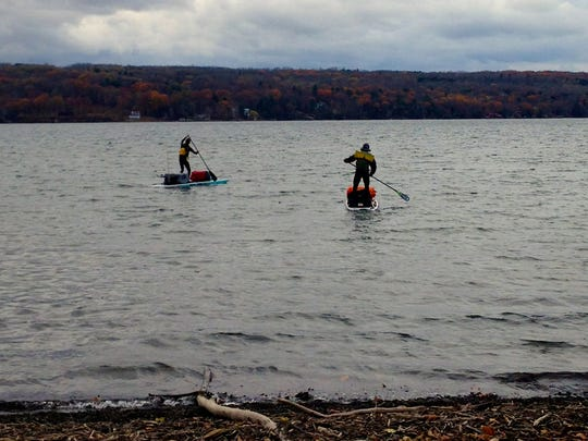 Gordon Middleton, left, and Christian Shaw, both of Ithaca, set off from Myers Point on Cayuga Lake on Nov 9 on an 11-day paddle board trip to sample the water for microplastic beads.