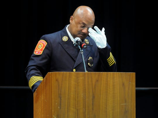 Lansing Fire Chief Randy Talifarro wipes his eye while