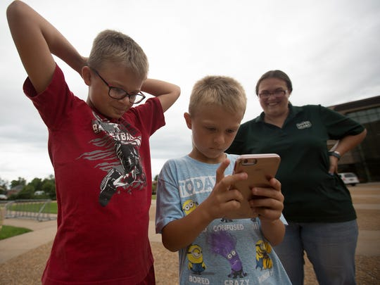 Amy Gurzynski of Plover, right, watches as her sons Dakota Boyer, 10, left, and Dawson Boyer, 7, play Pokemon Go at the Sundial at the University of Wisconsin - Stevens Point, Thursday, July 14, 2016.