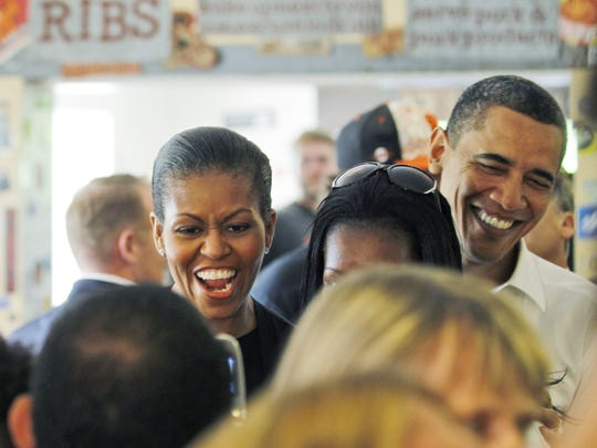 First lady Michelle Obama and President Barack Obama wait in line to order at 12 Bones Smokehouse in Asheville, April 23, 2010.(AP Photo/Alex Brandon)