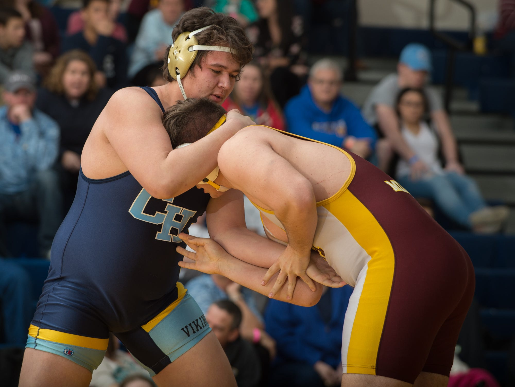 Cape Henlopen's Zach Flores, left, and Milford's Bryan Wynes battle for position in the 285 pound championship match at the Henlopen Conference wrestling tournament at Sussex Central High School.
