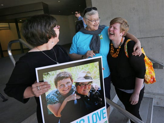 Victoria Smith Weiland, left, from Eugene, Ore., holds a picture of her and her partner Peggy McComb, as McComb hugs Aubrey Chonbold, right, on the steps of the Wayne L. Morse U.S. Courthouse Wednesday, May 14, 2014, in Eugene, Ore. A federal judge will hear arguments Wednesday about whether a national group can defend Oregon's ban on same-sex marriage because the state's attorney general has refused to do so. (AP Photo/The Register-Guard, Chris Pietsch)