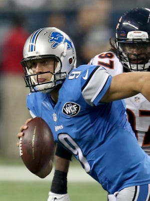 Lions QB Matthew Stafford runs by Bears DL Willie Young during the second half of the Lions' win Thursday.