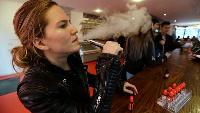 Talia Eisenberg, co-founder of the Henley Vaporium, uses her vaping device Feb. 20, 2014, in New York.