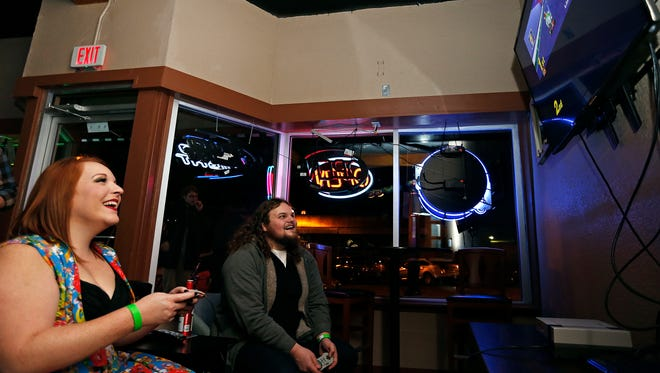 Erika Keithley (left) and John Kirk play a slightly one-sided game of Mario Kart at the newly opened Moon City Pub in Springfield, Mo. on Feb. 12, 2016.