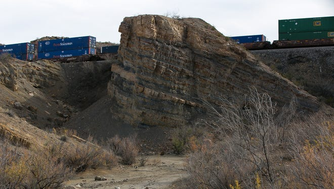 A train passes by behind Track 1 of the Insights Science Center New Mexico Dinosaur Trackways which is located near the starting area of the proposed Rio Grande Trail.