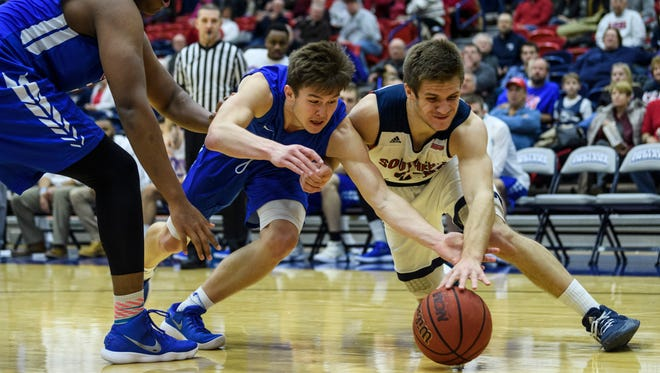 Ohio Valley's Christian Alley (10) and USI's Alex Stein (20) fight for possession of the ball in Evansville, Ind., Sunday, Dec. 31, 2017. The Screaming Eagles defeated the Fighting Scots, 95-69, in their last non-conference game of the season.