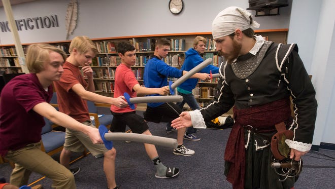 University of West Florida Fencing Club member, Brad Cramer, right, gives a group of students at Washington High School a lesson in sword fighting during the high school's Shake Fest Wednesday morning March 9, 2016.
